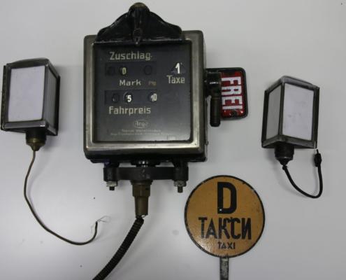 Altes Taxameter mit alten Taxilampen und einem Taxischild aus der SBZ